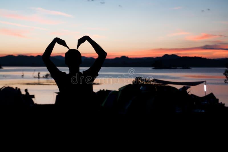 人剪影做了与暮色天空的肢体语言爱 图库摄影