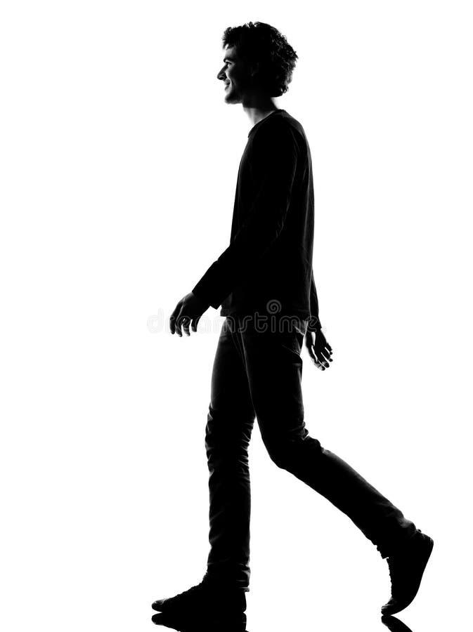人剪影微笑的走的年轻人 免版税图库摄影