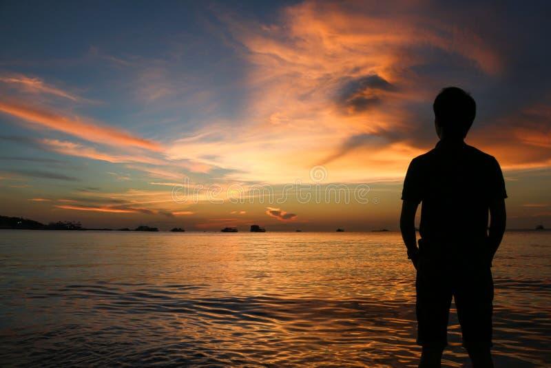 人剪影日落的在海滩 免版税库存图片
