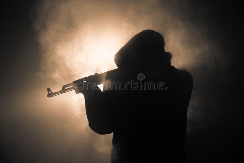 人剪影有准备好的攻击步枪的攻击在黑暗的被定调子的有雾的背景或危险匪盗黑佩带的巴拉克拉法帽的 免版税库存图片