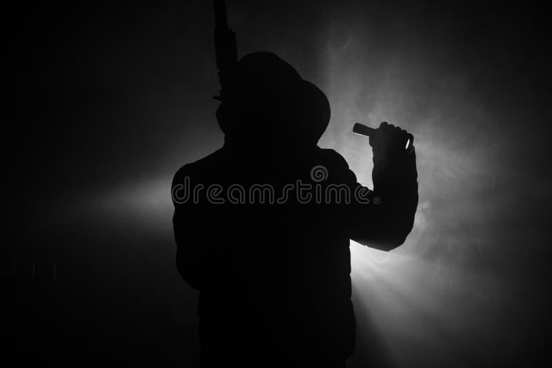 人剪影有准备好的攻击步枪的攻击在黑暗的被定调子的有雾的背景或危险匪盗黑佩带的巴拉克拉法帽的 库存照片