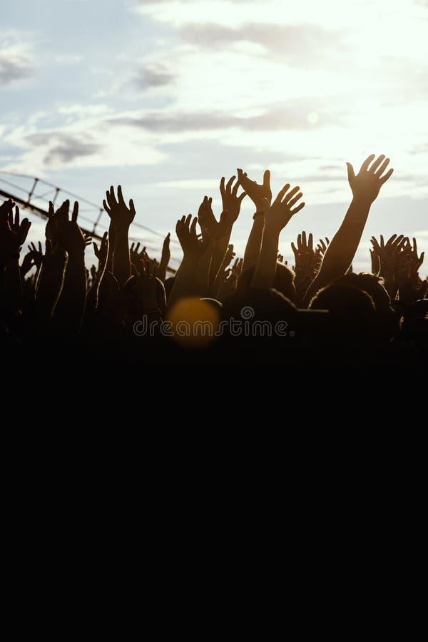 人剪影用被举的人手,海滩党暑假假期概念 免版税库存图片