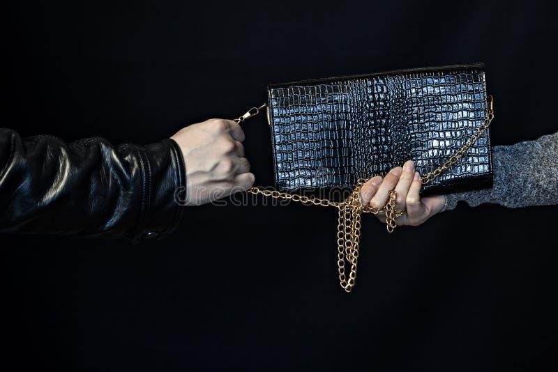人劫掠从妇女,黑人背景罪犯的手的一个提包 库存照片