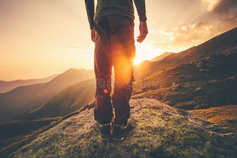 年轻人单独站立与在背景的日落山的旅客脚 免版税图库摄影