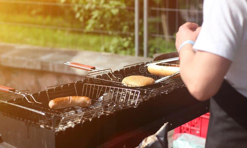 人厨师香肠和小圆面包热狗和汉堡的在户外格栅 免版税库存图片