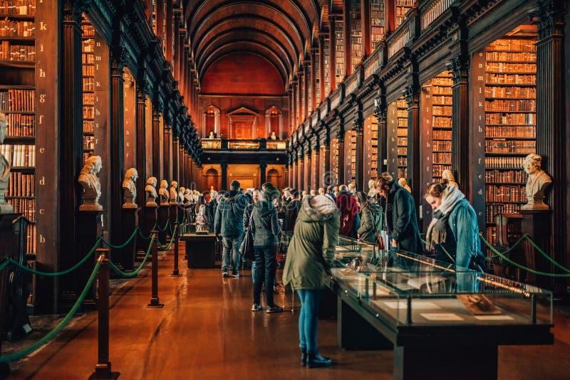 人参观著名长的屋子在老图书馆里在三一学院都伯林,爱尔兰 免版税图库摄影