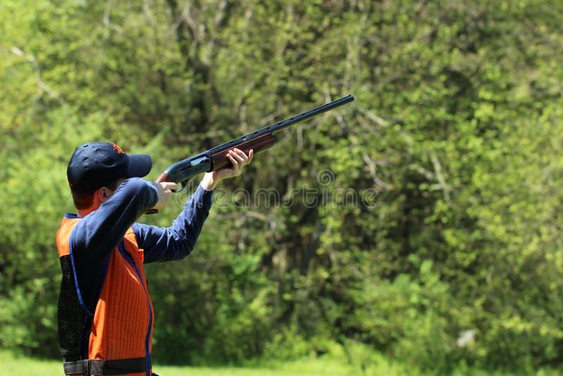 年轻人双向飞碟射击 免版税库存照片