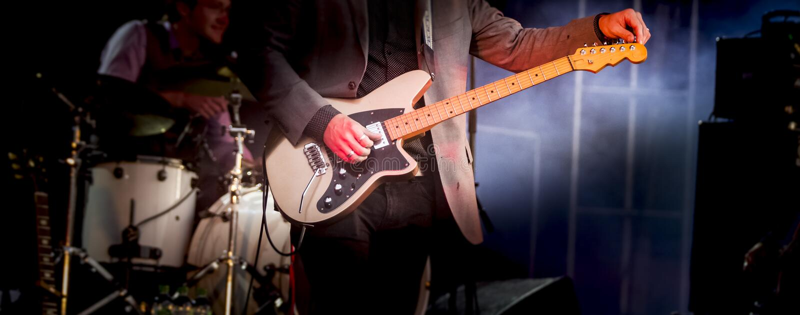 人吉他弹奏者执行在阶段摇滚音乐的低音吉他仪器 库存图片