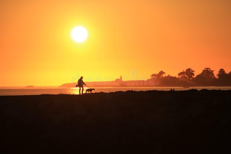 人和他的狗灯塔日落 免版税库存图片