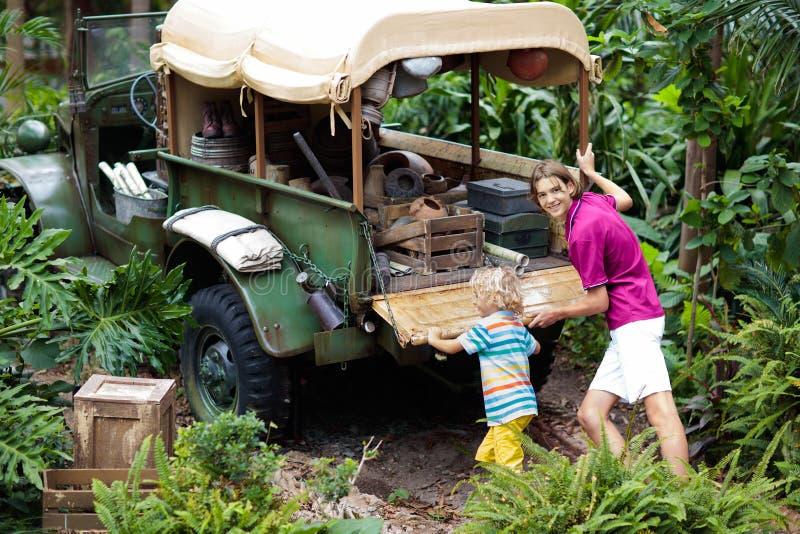 人和儿童在泥困住的推挤汽车在密林 推挤公路车辆的家庭困住在泥泞的土地形在热带森林里 免版税库存照片