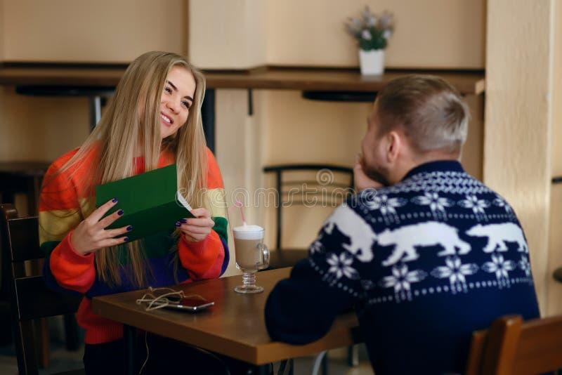 人和女孩饮料咖啡在咖啡馆,人给了女孩一个绿色信封以惊奇,妇女是非常愉快的,a 图库摄影