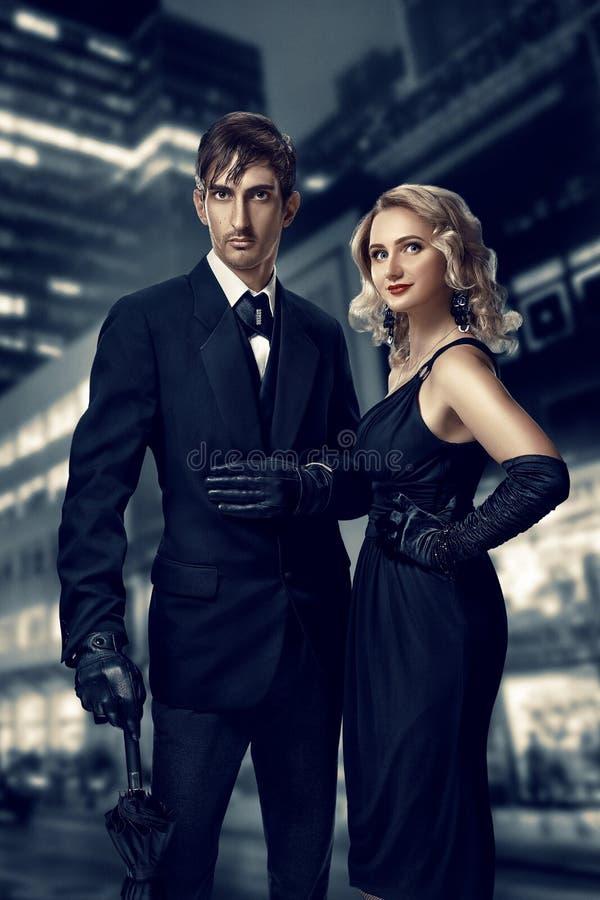 人和妇女侦探和间谍 努瓦尔的影片 反对夜城市的背景的减速火箭的样式时尚画象 库存照片