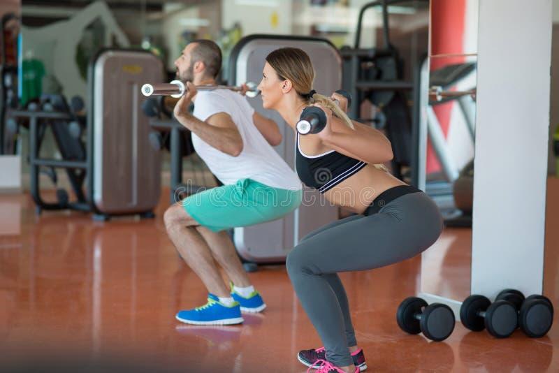 年轻人和妇女有屈曲肌肉和做肩膀的杠铃的按蹲坐在健身房 免版税库存照片