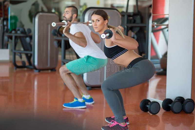 年轻人和妇女有屈曲肌肉和做肩膀的杠铃的按蹲坐在健身房 库存图片