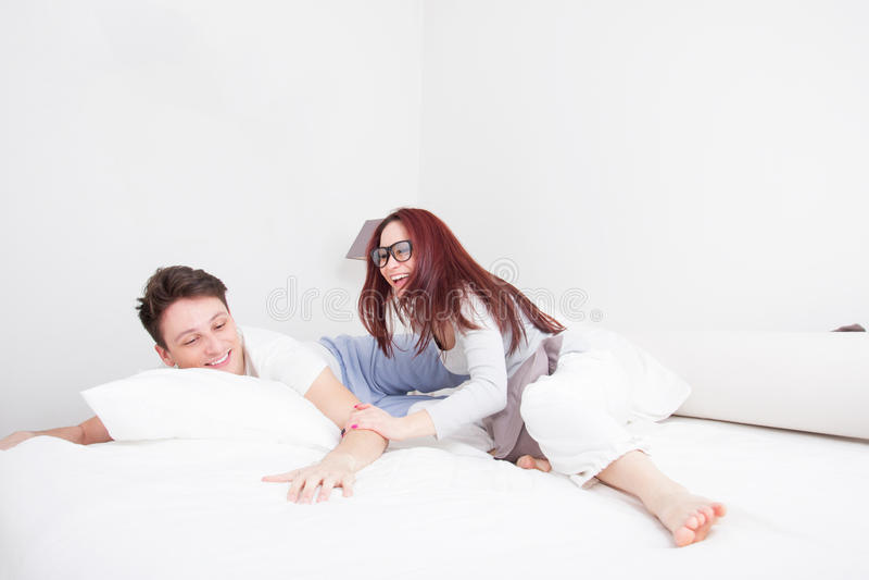 年轻人和妇女枕头战微笑的 免版税图库摄影