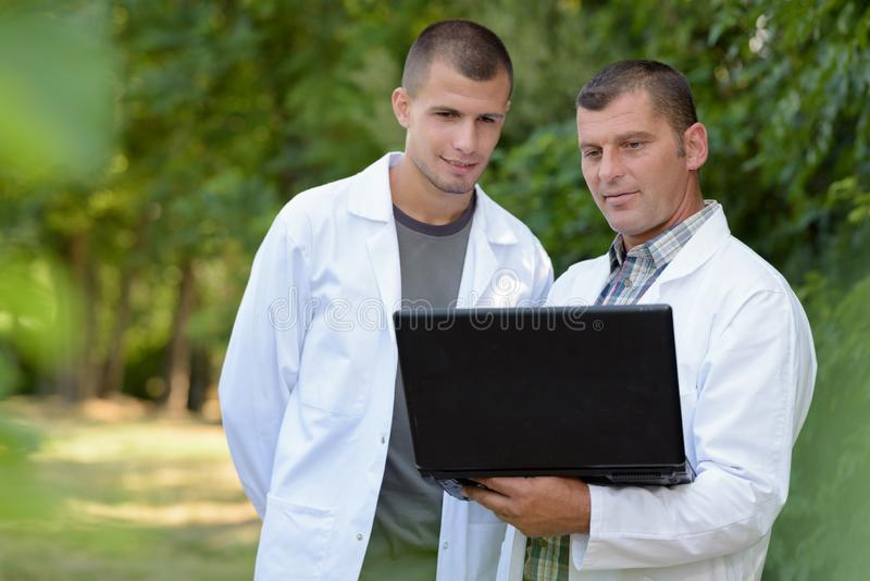 人和学徒白色外套的使用膝上型计算机 库存照片