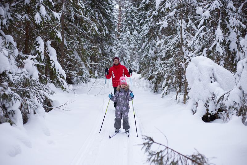 人和孩子在冬天滑雪在森林里 免版税库存照片