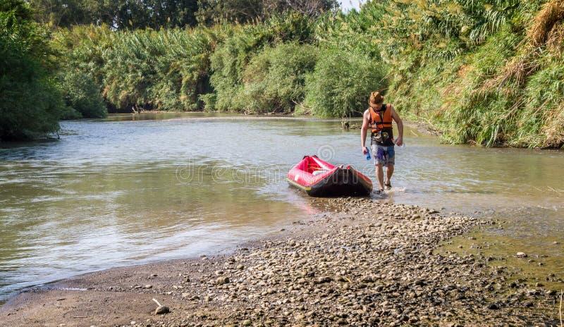 人和小船在约旦河 库存图片