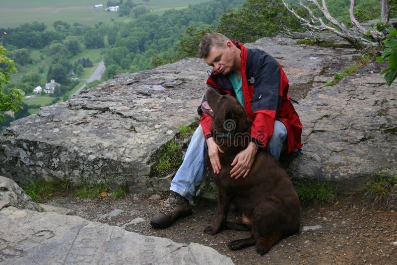 人和忠诚的狗在山峰 免版税库存图片