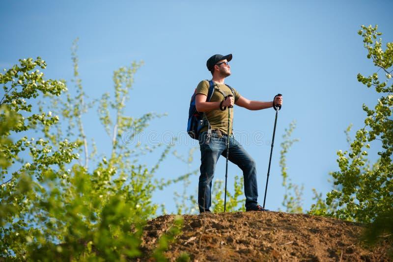 人和拐杖的图片有背包的在小山的 免版税库存照片