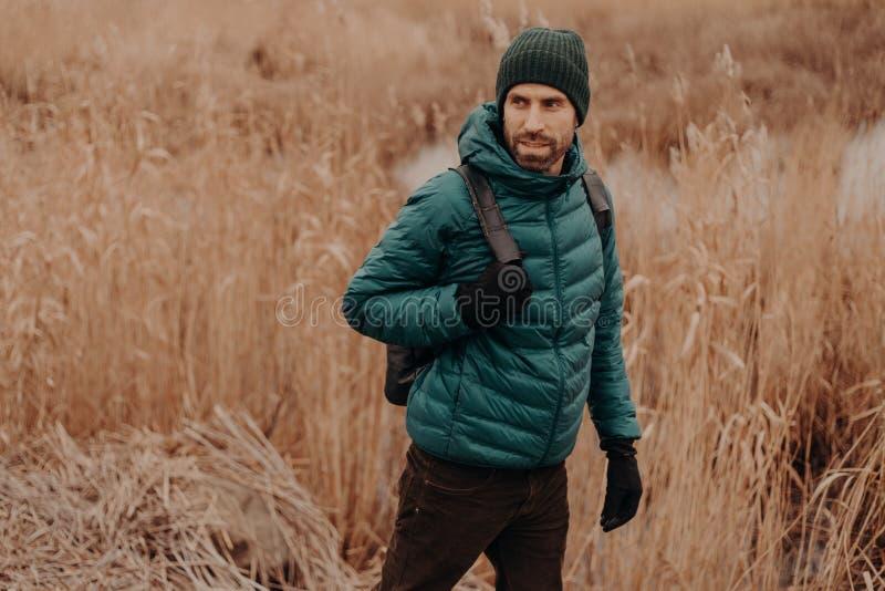 人和旅途概念 在温暖的夹克和头饰穿戴的帅哥射击,走外部,看殷勤地在旁边, 库存照片