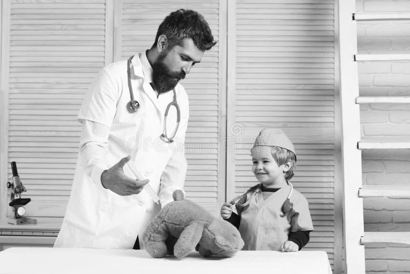 人和男孩有注射器的在木背景 父亲和孩子与扮演医生的愉快的面孔 图库摄影
