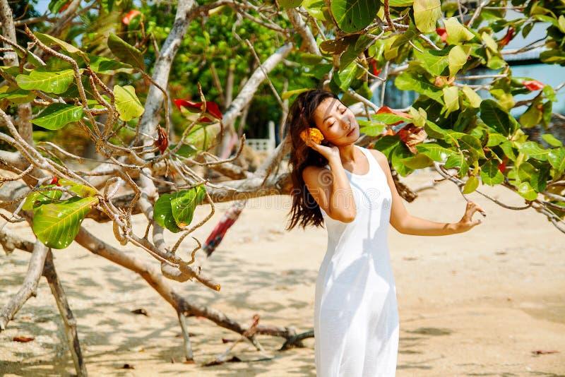 人和自然的互作用 海滩的美丽的亚裔妇女 免版税库存图片