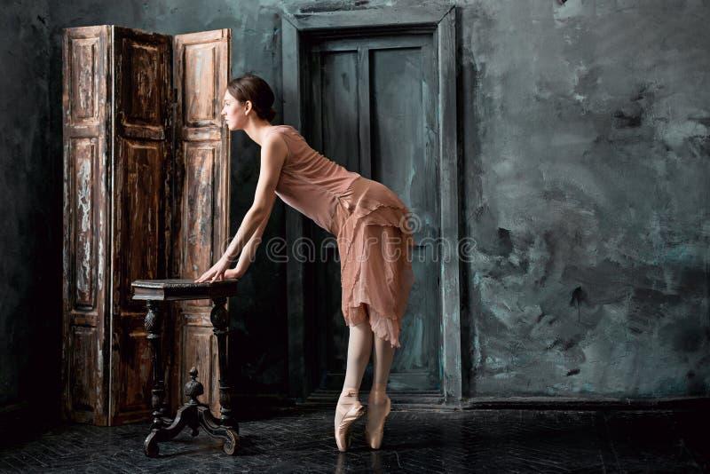 年轻人和难以置信地美丽的芭蕾舞女演员是摆在和跳舞在一个黑演播室 免版税库存图片
