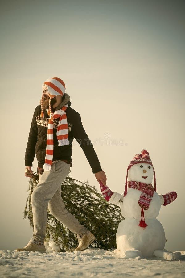 人和雪雕佩带的帽子和围巾 库存图片