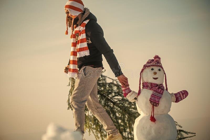 人和雪雕佩带的帽子和围巾 免版税图库摄影
