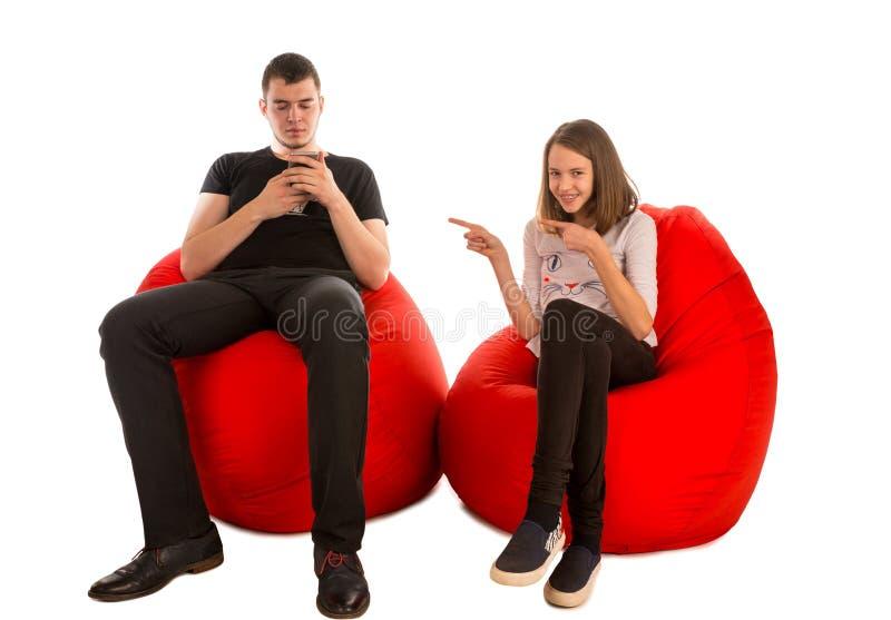 年轻人和滑稽的女孩坐红色装豆子小布袋椅子 库存照片