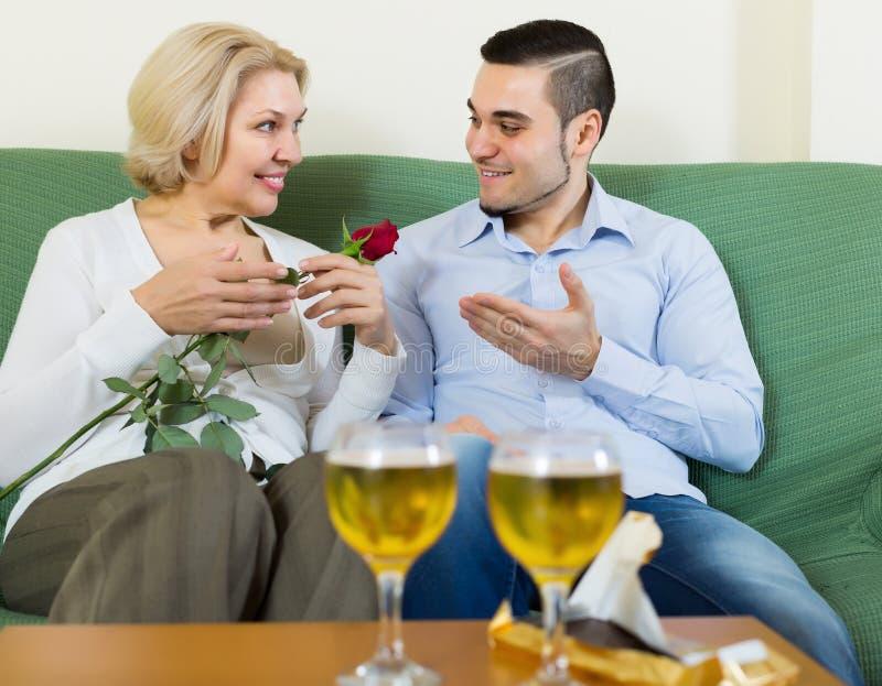 人和年长妇女饮用的酒和微笑 免版税图库摄影