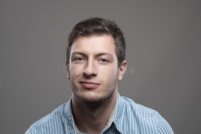 年轻人喜怒无常的特写画象蓝色衬衣的有假笑微笑的 图库摄影