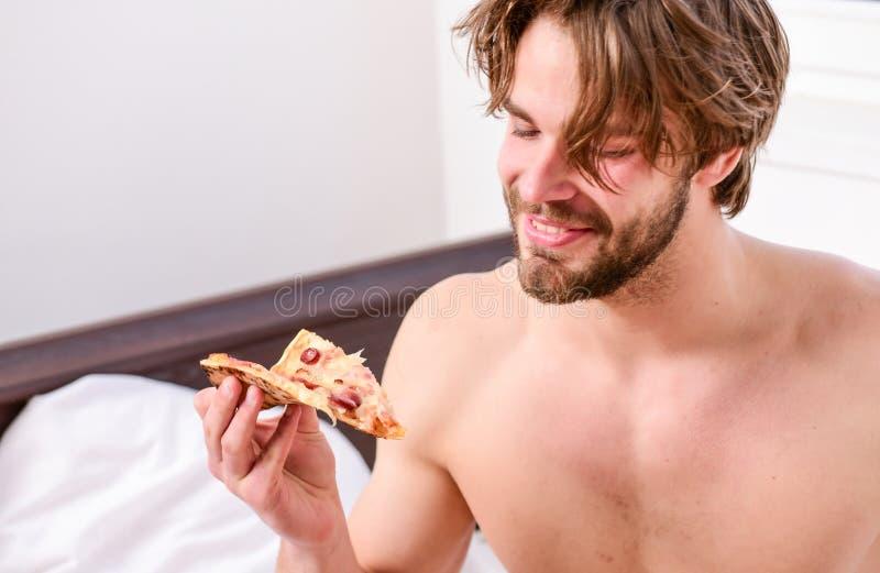 人喜欢在家休息与裸体和比萨的早餐年轻人的比萨 人在卧室拿着比萨箱子坐床 免版税库存照片