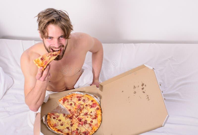 人喜欢早餐断裂饮食概念的薄饼 人在卧室或旅馆客房拿着薄饼箱子坐床 食物交付 库存图片