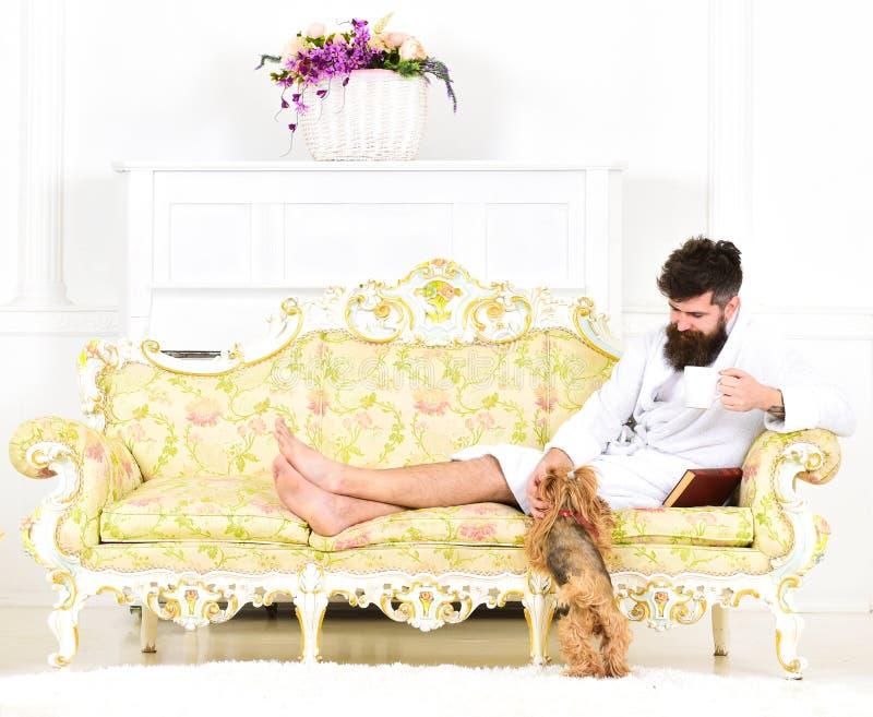 人困在浴巾在豪华旅馆里喝咖啡在早晨,白色背景 有胡子和髭的人享用 库存图片