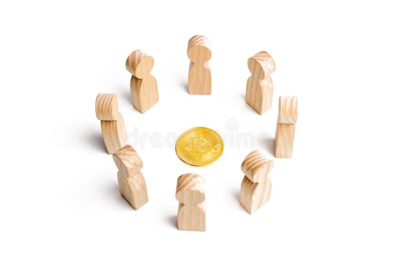 人圈子在白色背景的一枚bitcoin硬币附近站立 Cryptocurrency和blockchain技术 库存照片