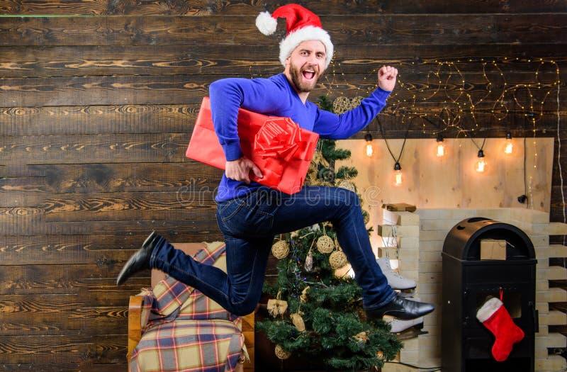 人圣诞老人准时交付礼物的帽子仓促 被传播的幸福和喜悦 行动跃迁的有胡子的人 交付圣诞节 免版税库存照片