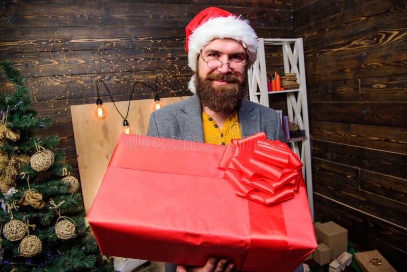 人圣诞老人帽子交付礼物 被传播的幸福和喜悦 有镜片的有胡子的人运载当前箱子 交付圣诞节 免版税库存照片