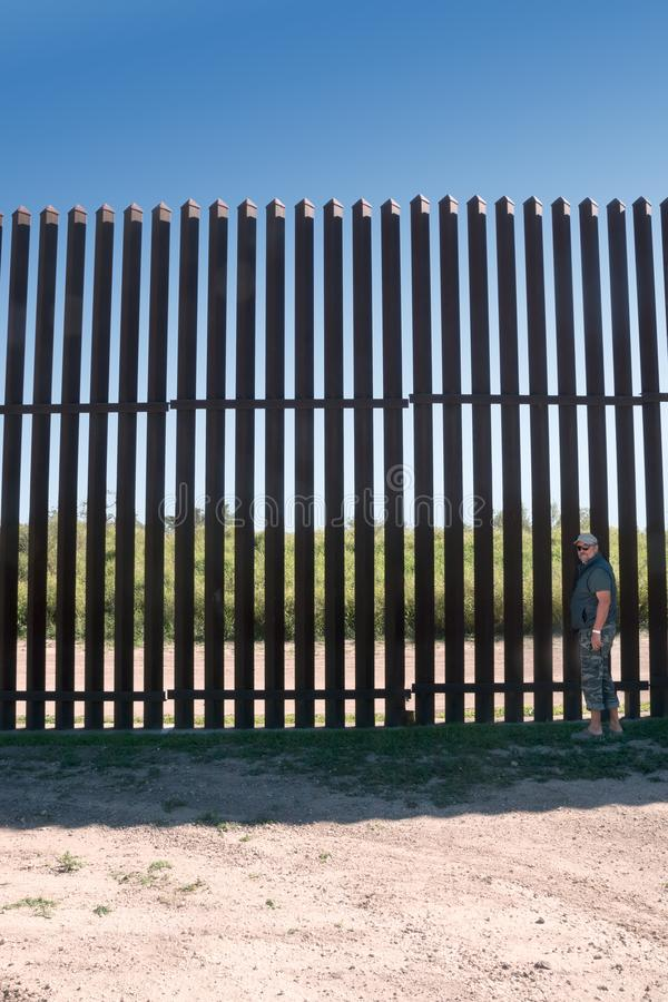 人在一个新的铁Mexico–美国障碍附近站立在乡下得克萨斯 免版税库存图片