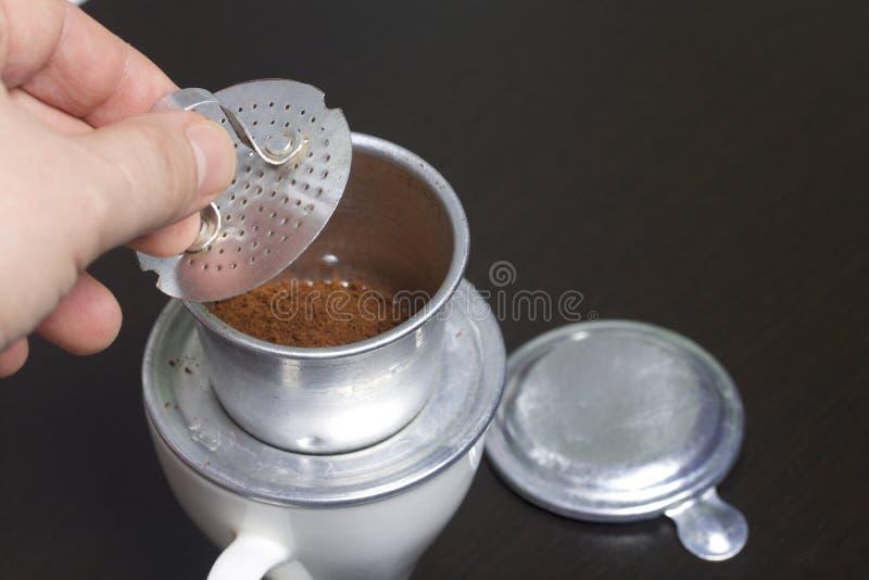 人在一个白色杯子安装了咖啡的越南酿酒者 他用碾碎的咖啡填装了它并且按了它与筛子 免版税库存图片