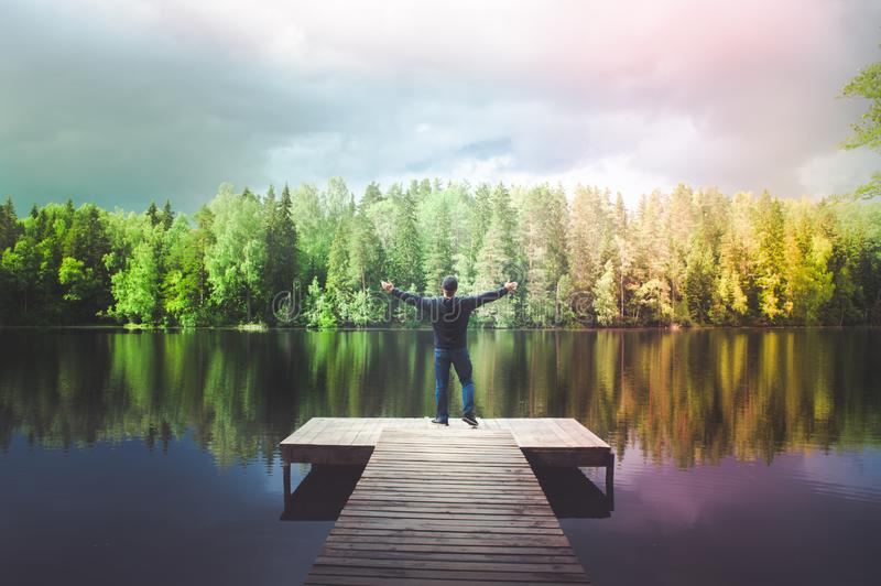 人在一个美丽的湖,享有生活的年轻人的码头站立,他的胳膊打开,在湖的一条彩虹 免版税库存照片