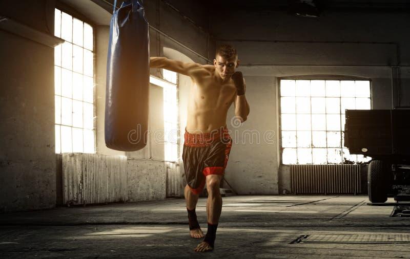 年轻人在一个老大厦的拳击锻炼 库存照片