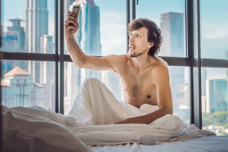 人在一栋公寓的早晨醒在市中心以摩天大楼为目的并且使用智能手机 免版税图库摄影