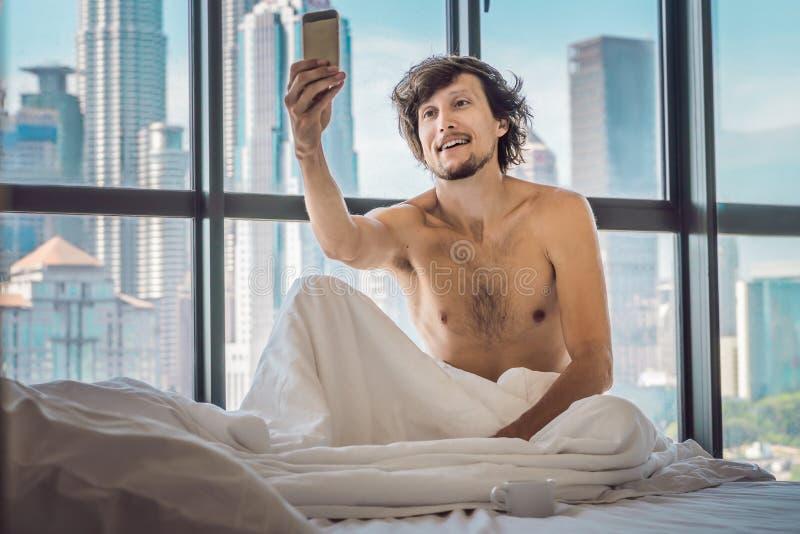 人在一栋公寓的早晨醒在市中心以摩天大楼为目的并且使用智能手机 免版税库存照片