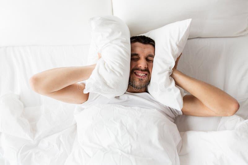 人在与遭受噪声的枕头的床上 免版税库存照片