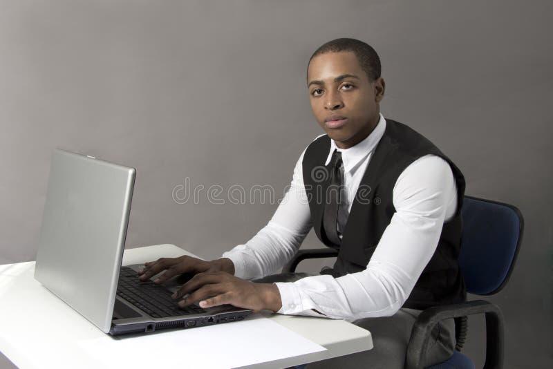 黑人在书桌后的办公室 免版税库存照片