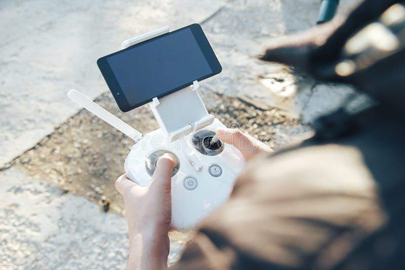 人在他的手上拿着一个寄生虫遥远的控制器 方形字体直升机RC特写镜头有天线的在飞行期间 飞行员拍空中照片 免版税库存图片