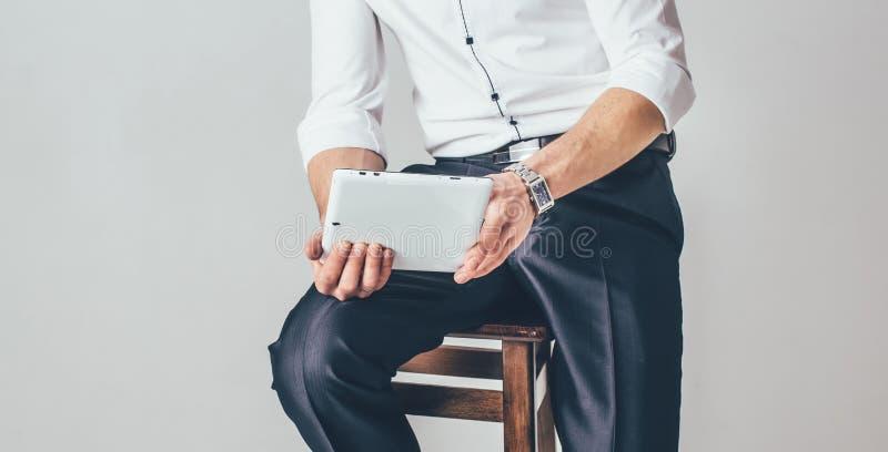 人在他的手上拿着一种片剂在白色背景 他坐在一炫耀的白色衬衫和裤子穿戴的椅子 库存照片