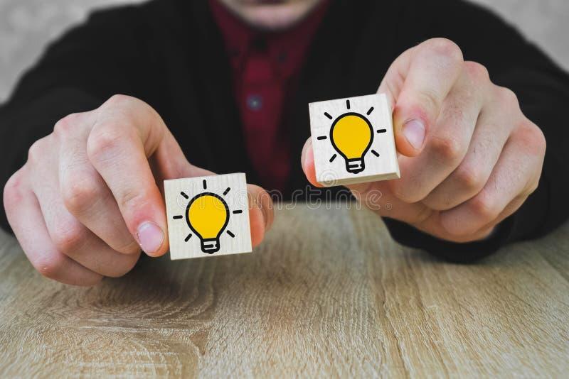 人在他的手上拿着与灼烧的灯的图片的两个木立方体象征一个新的想法的选择, 免版税库存照片